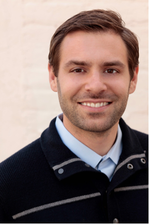 Headshot of a smiling Zack Almquist wearing a light-blue, collared shirt and a dark pullover against a cream-colored background