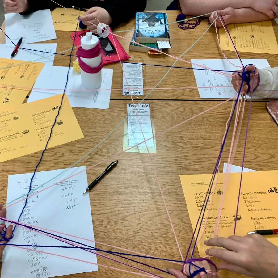 Hands of several youth holding a network model made of yarn above a table.