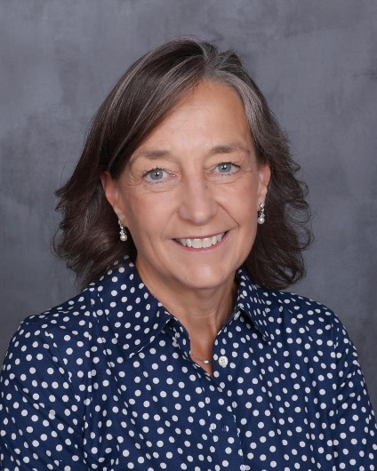Headshot of a person with shoulder-length hair, earrings, and a polka-dot blouse